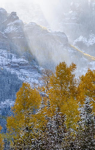 Sun breaking through  clouds on snowy autumn landscape in the Uncompahgre Range, Owl Creek Pass, Colorado