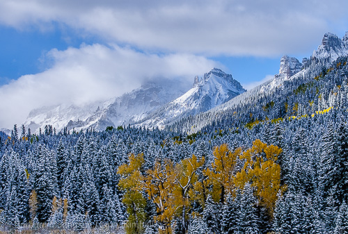 New snow and storm clouds shroud mountain tops along the Cimarron River
